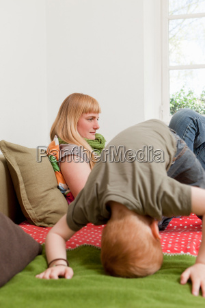 mother relaxing as son jumps on