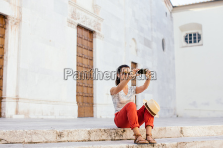 mid adult woman sitting taking selfie