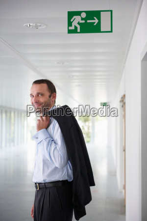 businessman in an empty office smiling