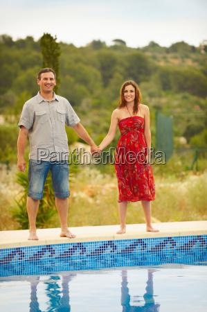 couple holding hands by swimming pool