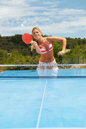 woman playing table tennis outdoors