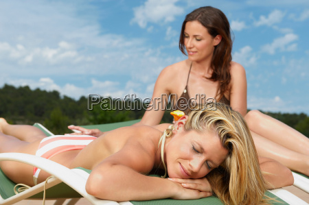 woman applying sunblock on female friend