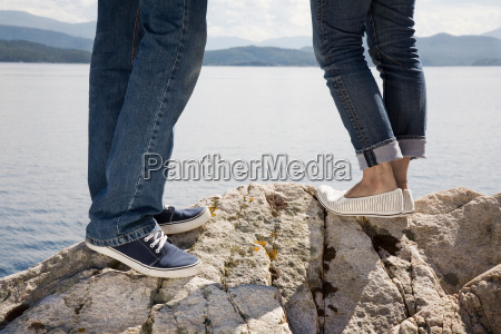 man and woman standing on rock