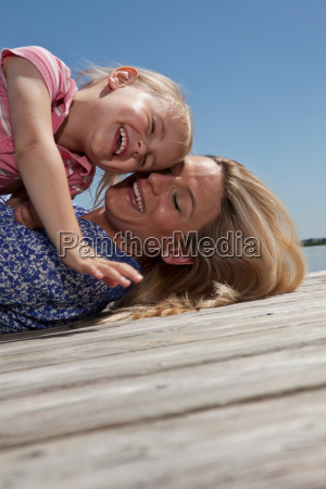 mother and daughter playing on dock
