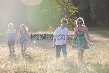 teenage couples walking in field