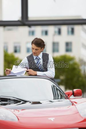 business man working near electric car