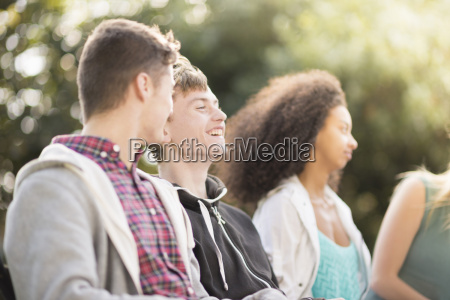 four young adult friends sitting talking