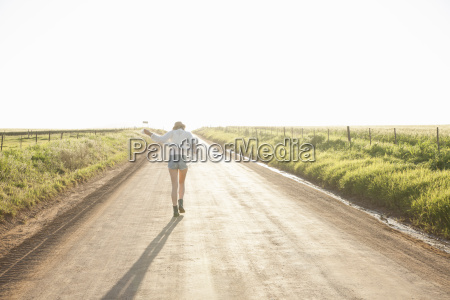 mid adult woman walking down country