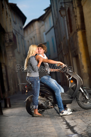 young couple kiss on scooter in