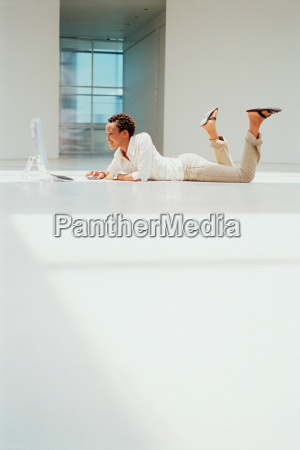 businesswoman using computer on floor