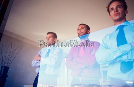 businessmen standing at office window