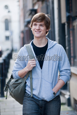young male walking and smiling