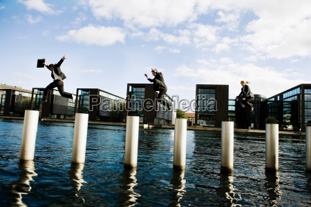 3 people jumping poles