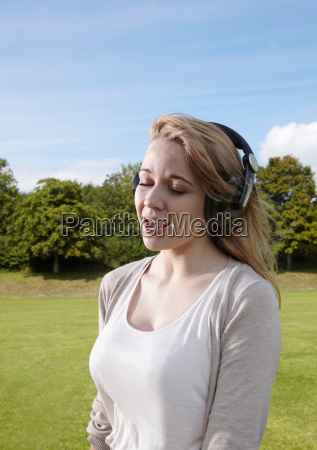 girl singing along to headphones
