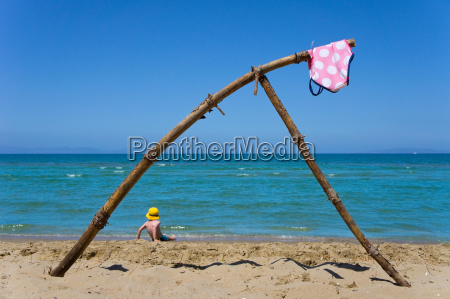 swimsuit hanging from driftwood on beach