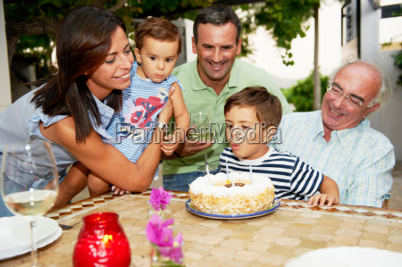 family blowing candles out on cake