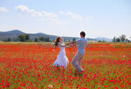 couple playing in field of poppies