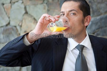 businessman drinking orange juice