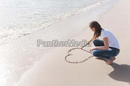 woman drawing heart shape in sand