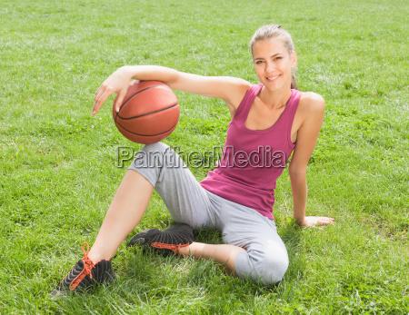 woman holding basketball on grass
