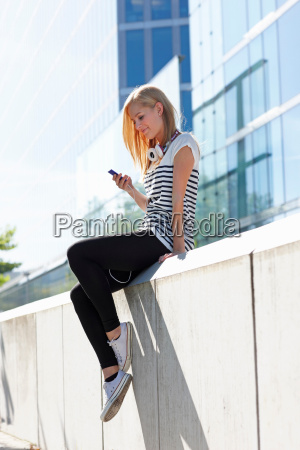 women sitting on wall with mp3