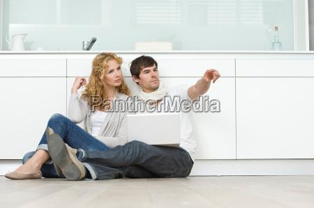 couple with laptop on kitchen floor