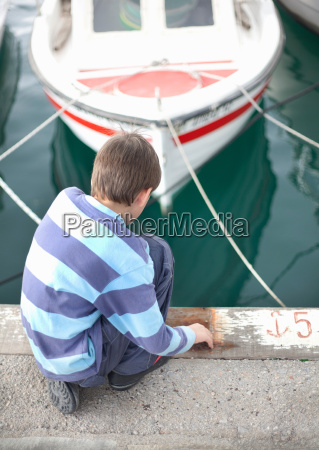 boy looking at boats in harbour