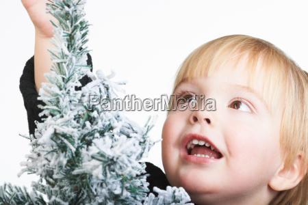 boy standing by a snowy tree