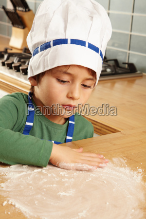 young boy playing with flour on