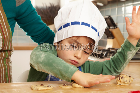 young boy making cookies in kitchen