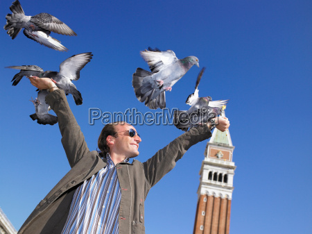 man with pigeons on his hands