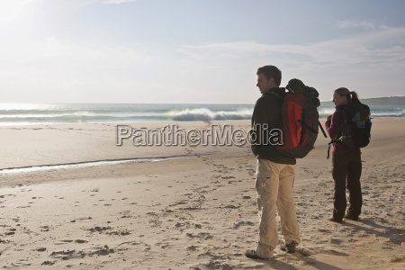 young backpacking couple at the beach