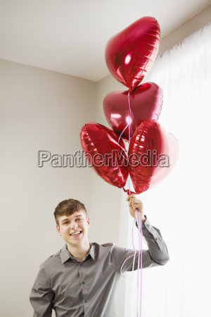 young man holding heart shaped balloons
