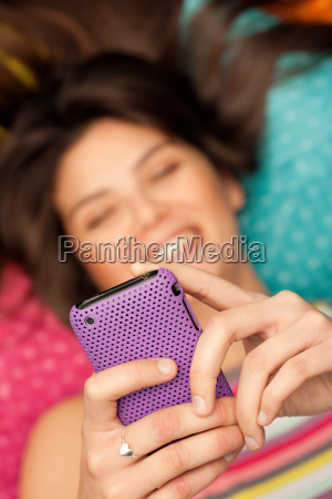 young woman checking her phone smiling