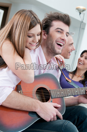 friends playing guitar and having fun