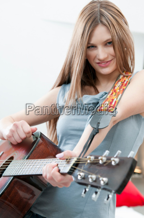 girl playing guitar with determination