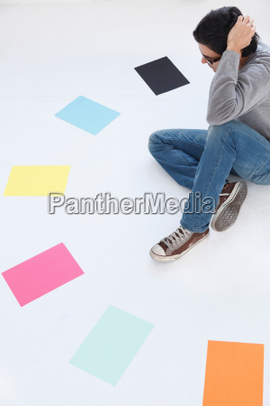 man looking at different coloured paper