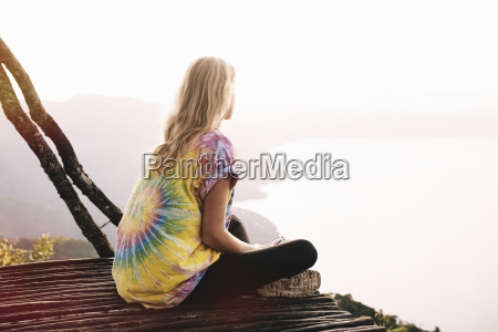 young woman sitting on balcony looking