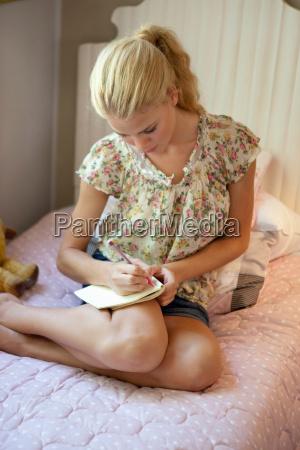 frau schreiben schreibend schreibt daheim zuhause