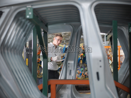 worker inspecting car parts in car