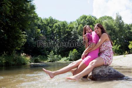 teenage girls sitting on rock in