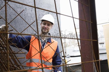 portraet eines fabrikarbeiters der stahlgitter in