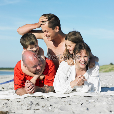family laying on beach towel together
