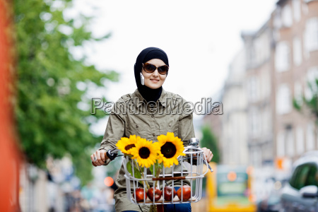 woman in headscarf biking on cell