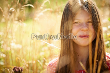 teenage girl smiling in tall grass