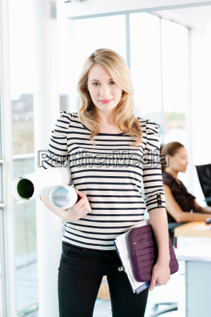businesswoman carrying blueprints
