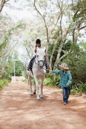 boy walking with girl on horse