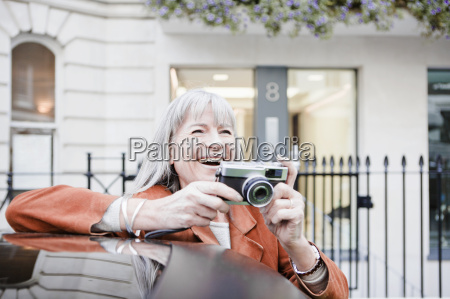 woman taking picture on city street