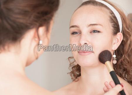 teenage girl having her makeup done