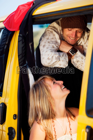 couple in a van smiling at